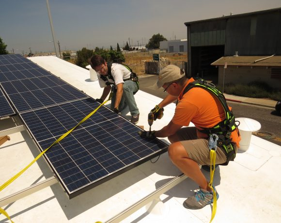 Volunteers attach panels to roof