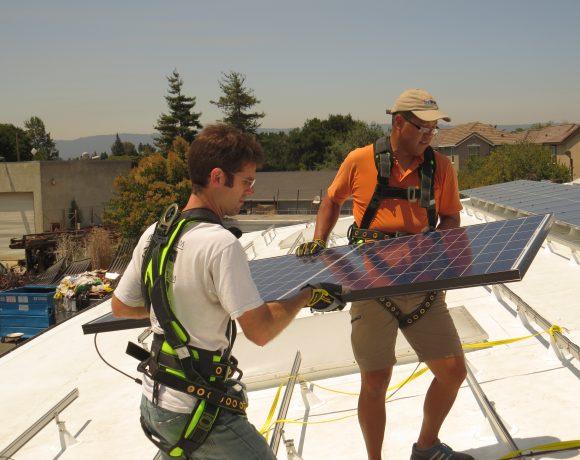 SunWork volunteers carry solar panel